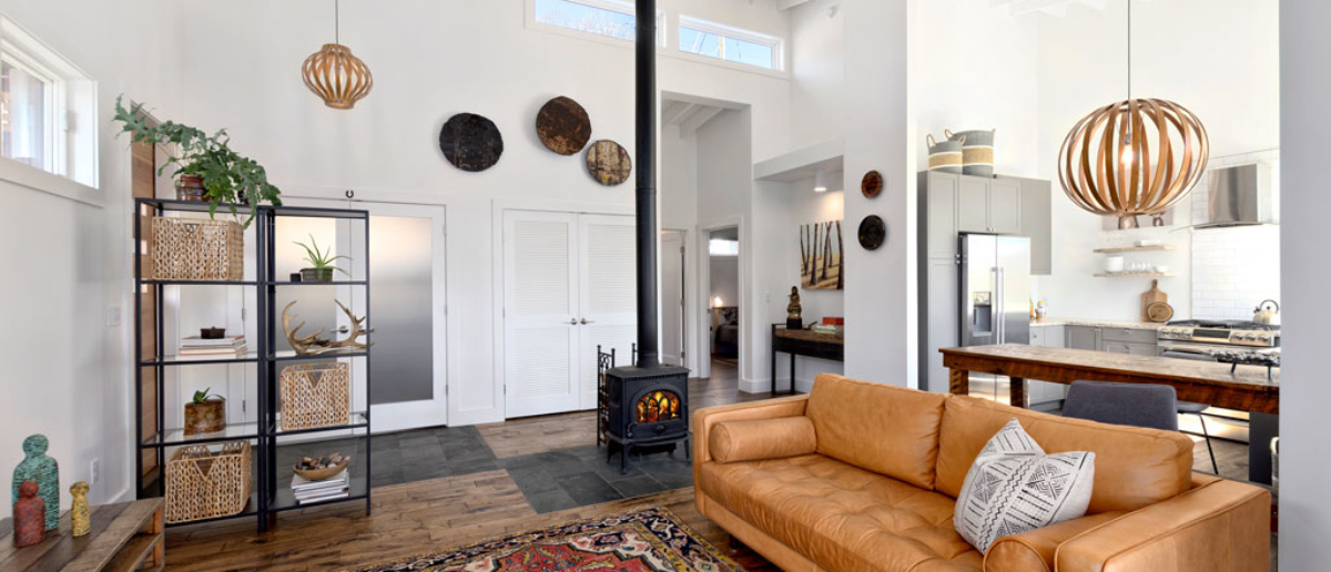 Large bright interior living area with wood stove and hardwood floors.