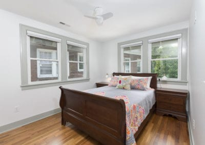 Bedroom with hardwoods floors and 4 large windows