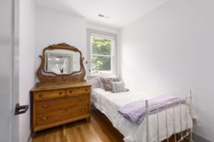 Small twin bed in room with large vanity dresser