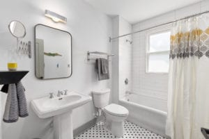 Bathroom with pedistal sink and tile floors. Shower/tub unit.