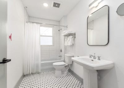 Bacthroom with black and white tile floor, pedistal sink, and bath/shower unit.
